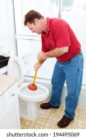 Man in his bathroom unclogging a toilet with a plunger.