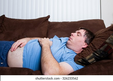 Man with his belly hanging out laying on the couch tired and asleep