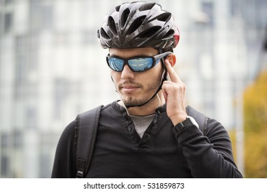 Man with his bike preparing to ride, with high builind in background