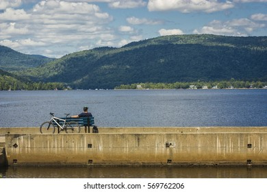 man with his bike sitting in front of water and mountains