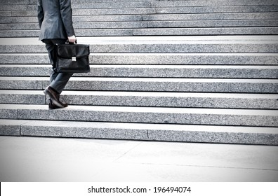 A man with his briefcase is walking up a set of cement steps.