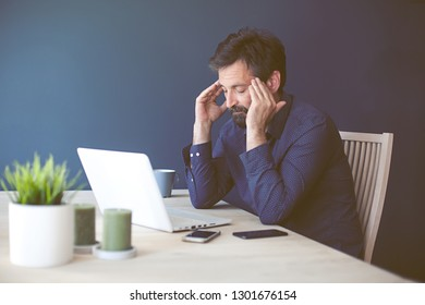 Man at his desk at home office looking stressed and tired