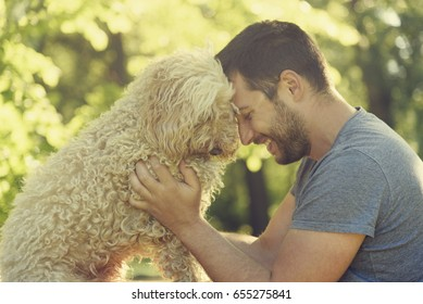 Man with his dog hugging and playing outdoor in the park. Young owner having fun with his pet in nature. Guy play with his animal friend. Friendship and love concept.