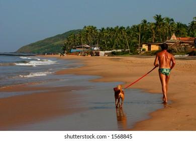 man and his dog on the beach, goa India.