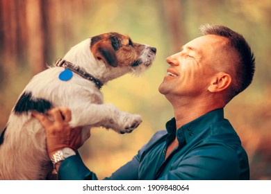 Man with his dog playing in the park. Owner hugs his pet.