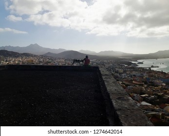 Man and his Dog Sitting on a Roof overlooking the City and Bay of Mindelo on the Island of Sao Vicente, Cape Verde Islands