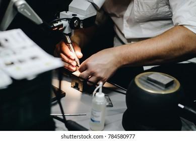 Man in his electrical workshop welding or soldering metal