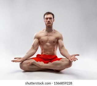 A man with his eyes closed and muscular body sitting in the lotus position
