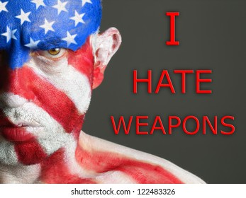 "Man with his face painted with the flag of USA and the text ""I hate weapons"". The man have an serious expression"