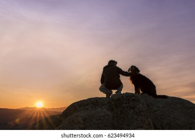 Man and his faithful companion watching the sunrise on top of the mountain