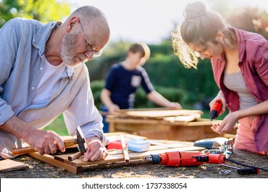 A man and his family are building wooden planters for their vegetable garden