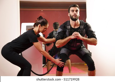 Man and his female personal trainer doing squats in EMS suit