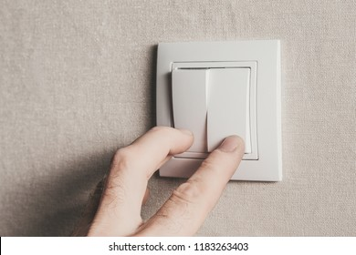 The man with his fingers turns on the light by pressing the white key