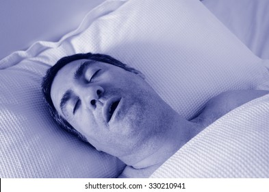 Man in his forties (40s) snoring in bed. Health care concept (BW)
