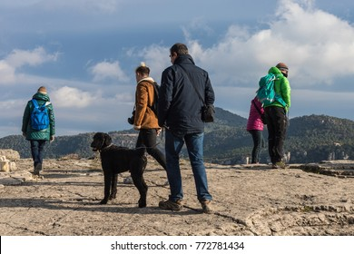 Man with his friend black dog, high up in the mountain after hours of hiking amid the wild nature