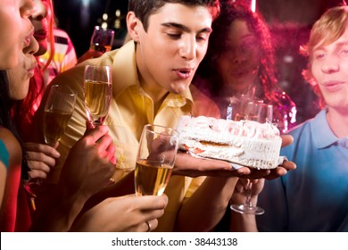 Man with his friends blow out candle on cake at birthday
