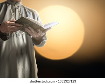 A man with his hand hold the Quran or Kuran ( the islamic holy book) on black background with rosary bead in ramadan night, muslim style and ramadan concept