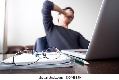man with his hand holding his face taking a brake from working with laptop computer and notebook with eye glasses on wooden desk. concept of stress / rest / tension / failed / discourage / depression
