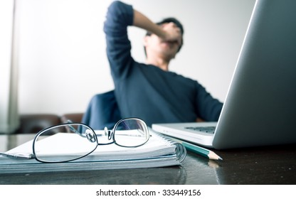 man with his hand holding his face taking a brake from working with laptop computer and notebook with eye glasses. concept of stress / rest / tension / failed / discourage / depressed. green filtered.