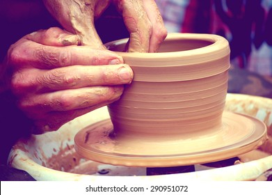 A man with his hands dub wall jug, which he sculpts out of clay on a circle