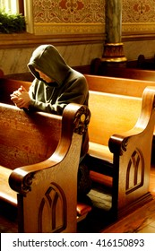 Man with his hands folded in prayer in a church.
