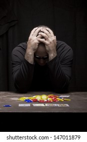 Man with his hands on his head is frustrated because he lost playing poker