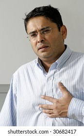 Man in his late thirties having a dose of heartburn or pains in his chest.