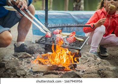 Man and his little daughter having barbecue in forest on rocky shore of lake, making a fire, grilling bread, vegetables and marshmallow. Family exploring Finland. Scandinavian summer landscape.
