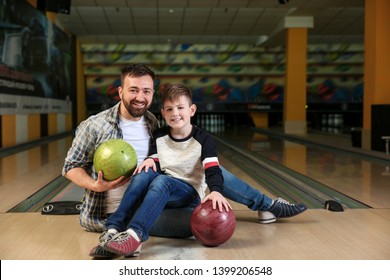 Man with his little son in bowling club
