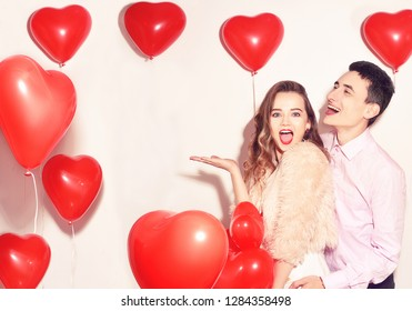 Man with his lovely sweetheart girl dance and have fun at Lover's valentine day. Valentine Couple Party. Background red balloons hearts. Love concept. Crazy. Empty copy space for your text.