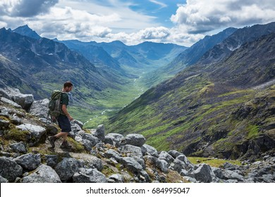 A man in his mid-20's hikes with a daypack down a steep trail overlooking the Little Susitna River in the Gold-Mint Trail Valley of the Hatcher Pass area in the Talkeetna Mountain Range of Alaska.