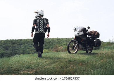 Man and his motobike. Rear view, Place for text, Touristic motorcycle with side bags and a tent. The concept of extreme recreation and camping.