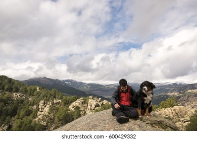 Man and his pet rests on the rock at the top of the mountain contemplating a beautiful landscape