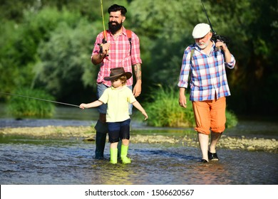 Man with his son and father on river fishing with fishing rods. Father teaching his son fishing against view of river and landscape. Men day