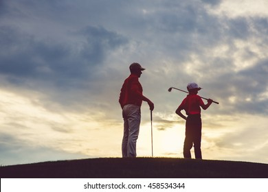man with his son golfers standing on golf course at sunset, back view
