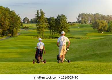 man with his son golfers walking on perfect golf course at summer evening, back view