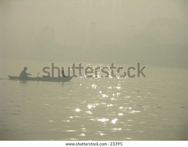 A man and his son with their boat in haze morning.