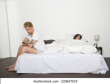 Man with his telephone while the wife sleeps