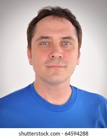 A man in his thirties is staring into the camera and looks calm and kind yet serious. He is wearing a blue t-shirt and is casual.