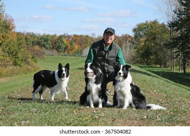 A man with his three border collies dogs