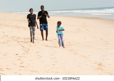 a man and his two children running by the sea with joy.