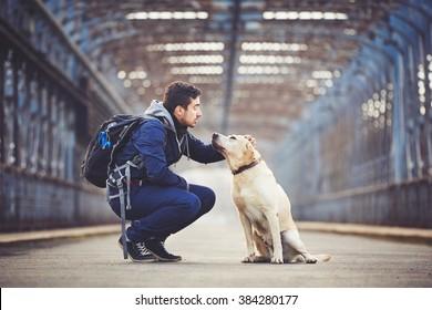 Man with his yellow labrador retriever on the old bridge