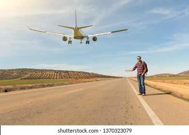 Man hitchhiking and airplane landing on the road - Travel concept with land and air travel together, unreal situation of aircraft landing on a straight road in Spain - Wanderlust and adventure