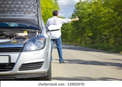 Man hitchhiking by a broken car