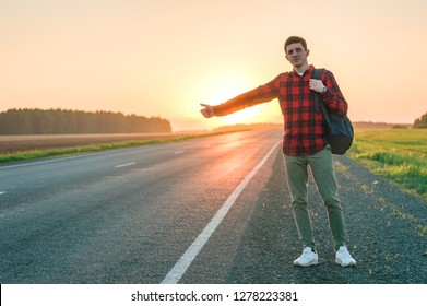 A man hitchhiking. He stands on the side of the road and votes with his thumb up to someone to stop and pick him up. He has a backpack on his shoulder. Road among fields.