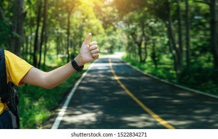 Man hitchhiking on road in Spring