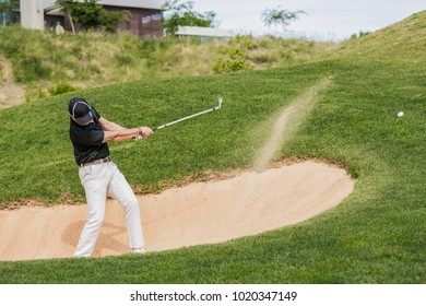 Man hitting golf ball out of a bunker