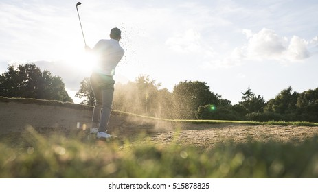 Man hitting golf shot in a bunker on a golf course