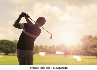 Man hitting golf shot with club on course at evening time.