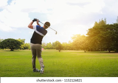Man hitting golf shot with club on course while summer in the sun.